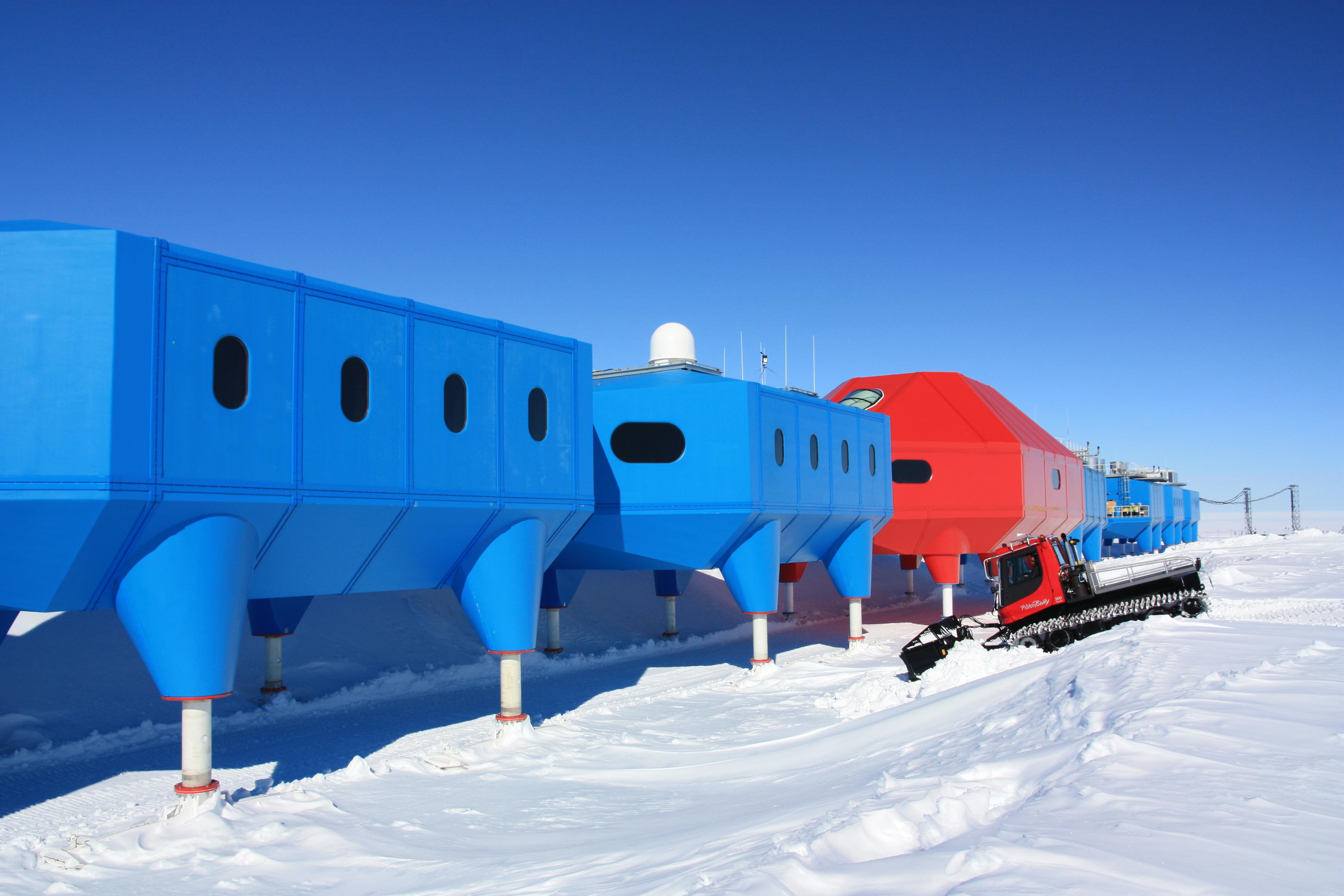 Mehrere Gebäudekomponenten schließen sich zu einem langen Komplex zusammen und bilden die Forschungsstation. Die Komponenten stehen jeweils auf Stelzen und sind rot. In der Mitte ist eine größere und rote. Rechts davon fährt ein Schneemobil.