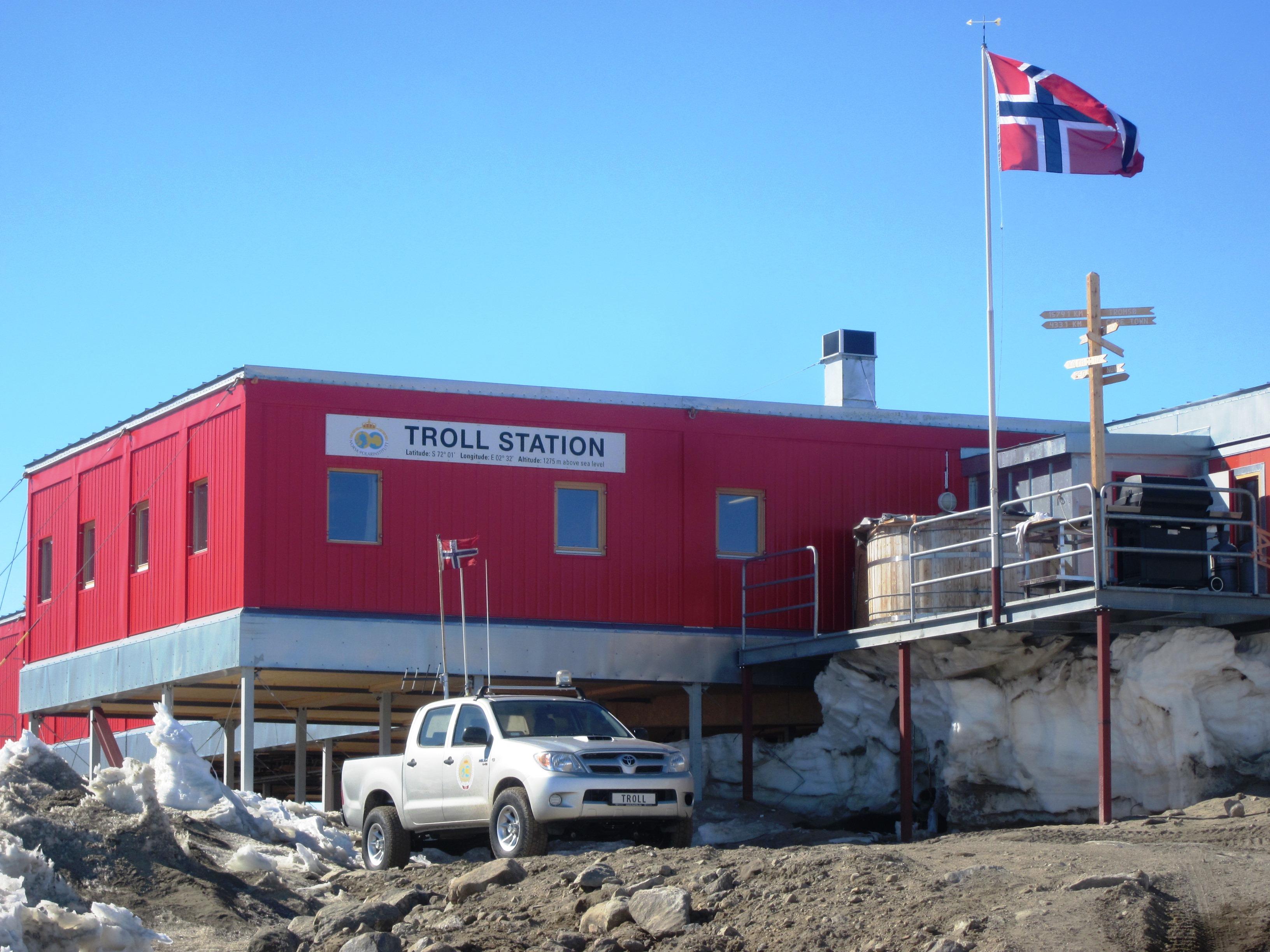 Ein Pick-Up mit Messgeräten auf der Ladefläche steht vor der norwegischen Antarktisstation Troll. Die Station steht auf Stelzen und ist rot. Der Name steht an der Vorderseite auf einem großen Schild. Vor dem Eingang weht die norwegische Flagge.