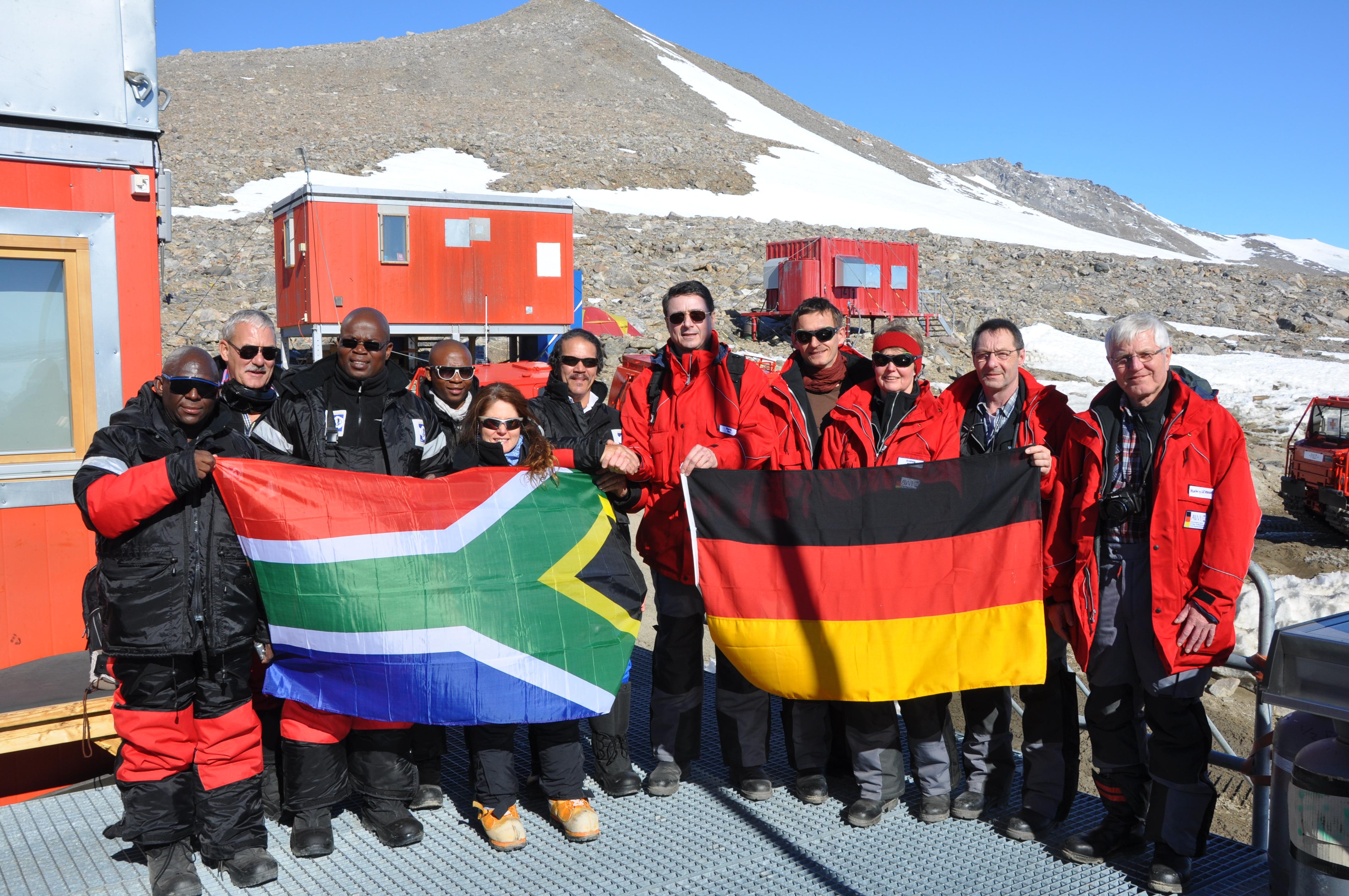 Vor einer Forschungsstation steht eine Gruppe von Männern und Frauen. Links die Gruppe aus Südafrika, recht die deutsche Gruppe. Beide halten ihre jeweilige Landesflagge in den Händen.