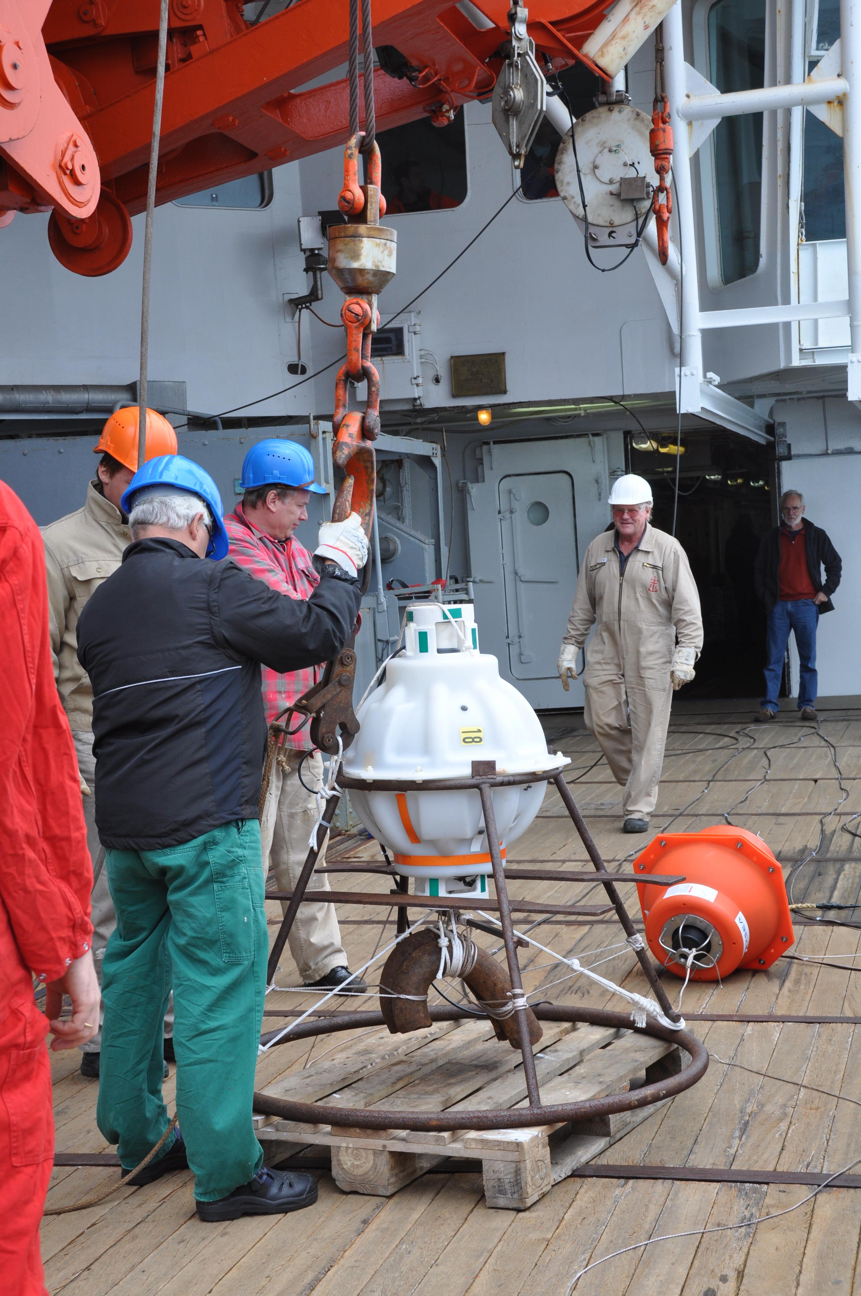 An Bord der Polarstern bereiten 5 Männer die PIES-Sonde auf ihren Einsatz vor. Die Sonde ist rundlich und hängt ein einem Kran, der sie zum Meer hinablässt.