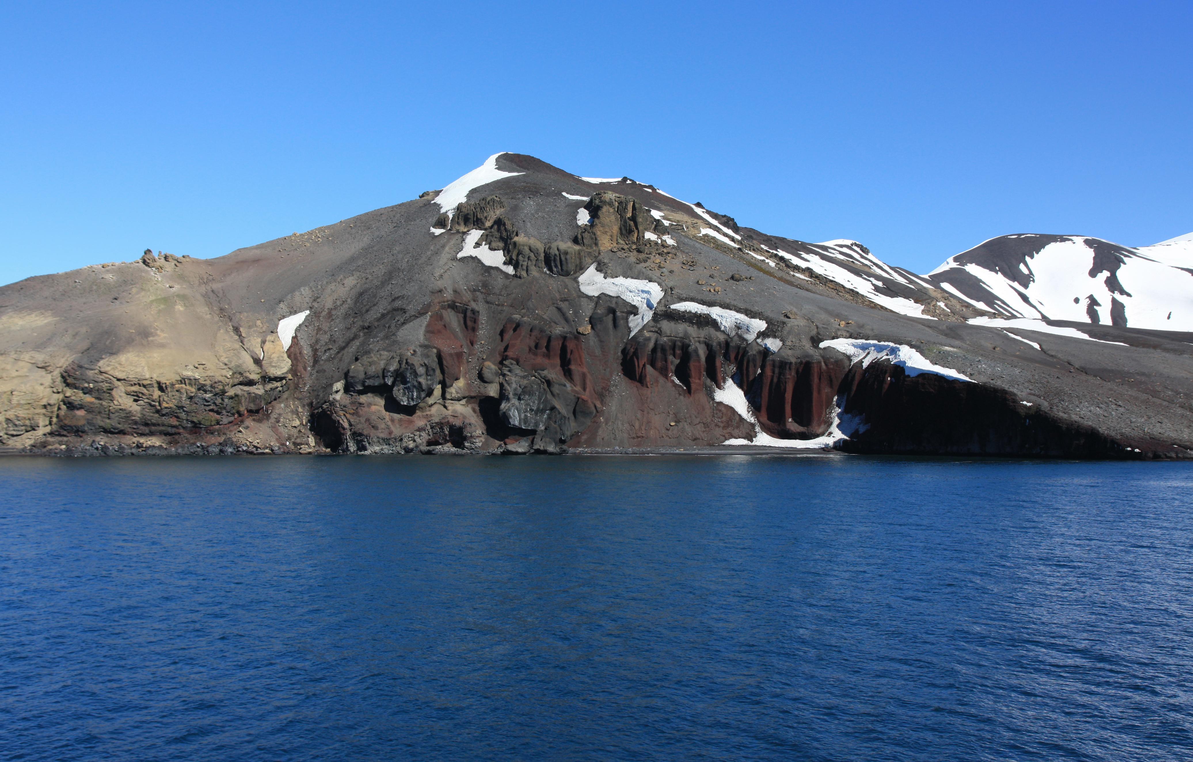 im Vordergrund des Bildes sieht man ruhiges antarktisches Meer vor einem Berg.