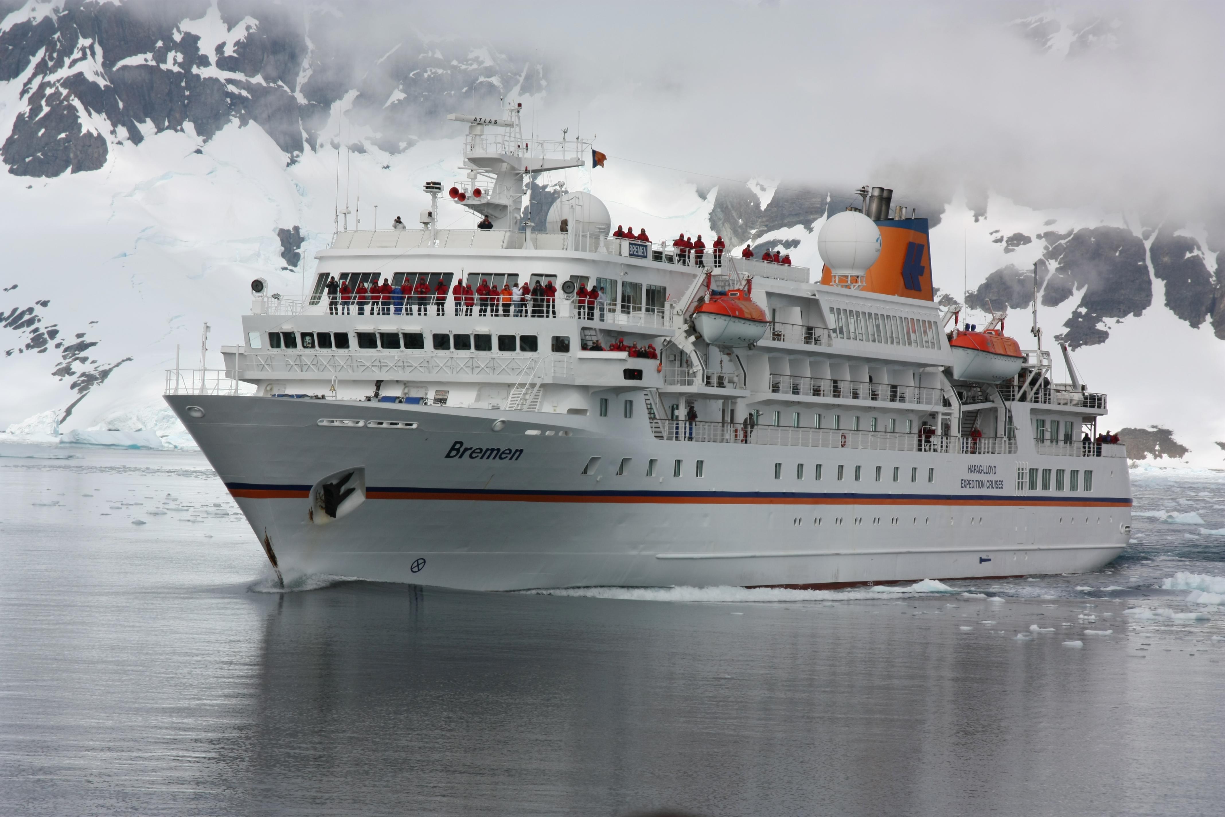 Das Kreuzfahrtschiff Bremen fährt durch antarktisches Gewässer. Hinter ihr ragt eine steile schneebedeckte Felswand auf. Die Wolken hängen sehr tief. Auf dem Schiff stehen Menschen in Kälteschutzanzügen.