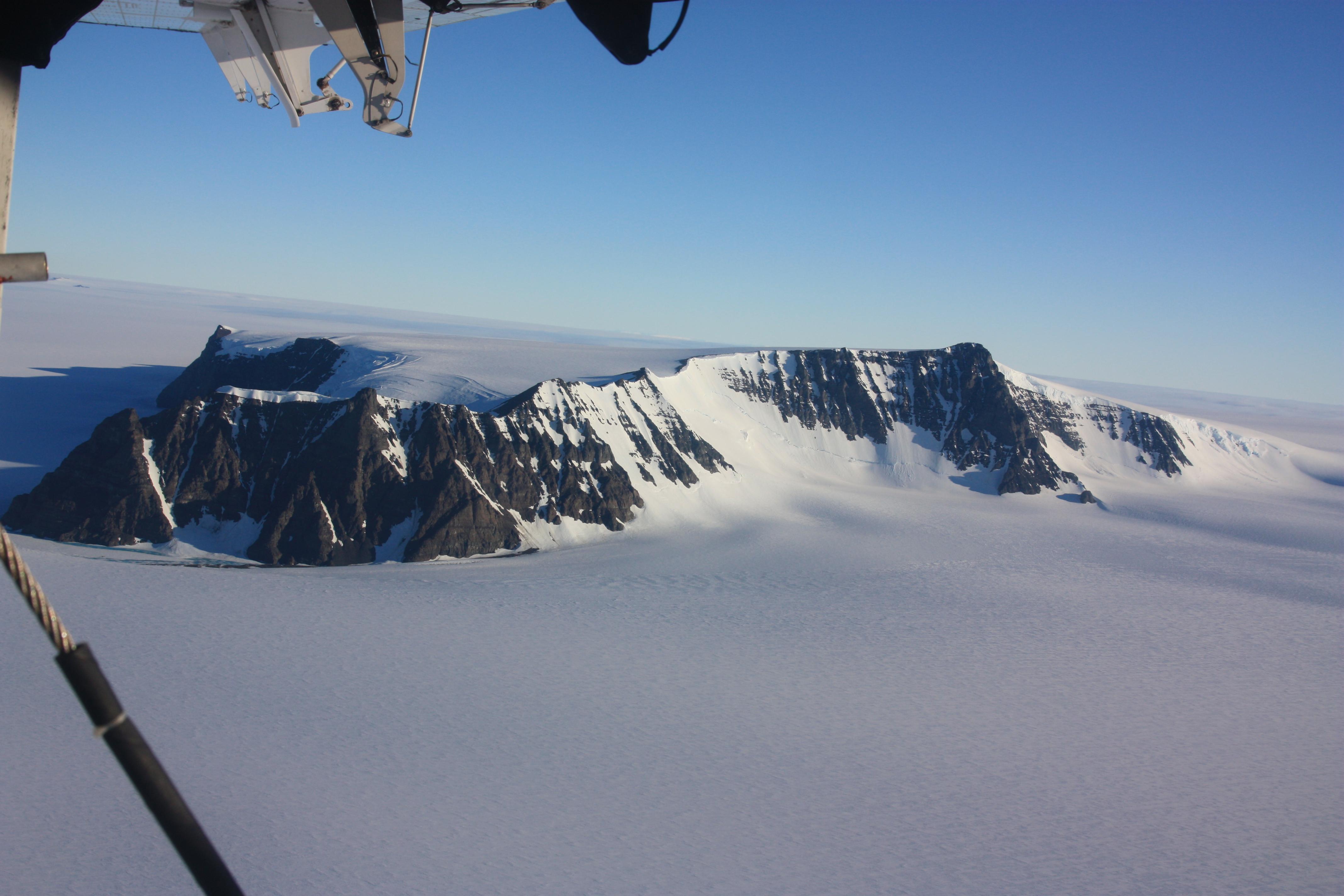 Blick aus einem Flugzeug über Königin-Maud-Land in Alaska. Man sieht eine schnee- und eisbedeckte Landschaft und zwei Berge.