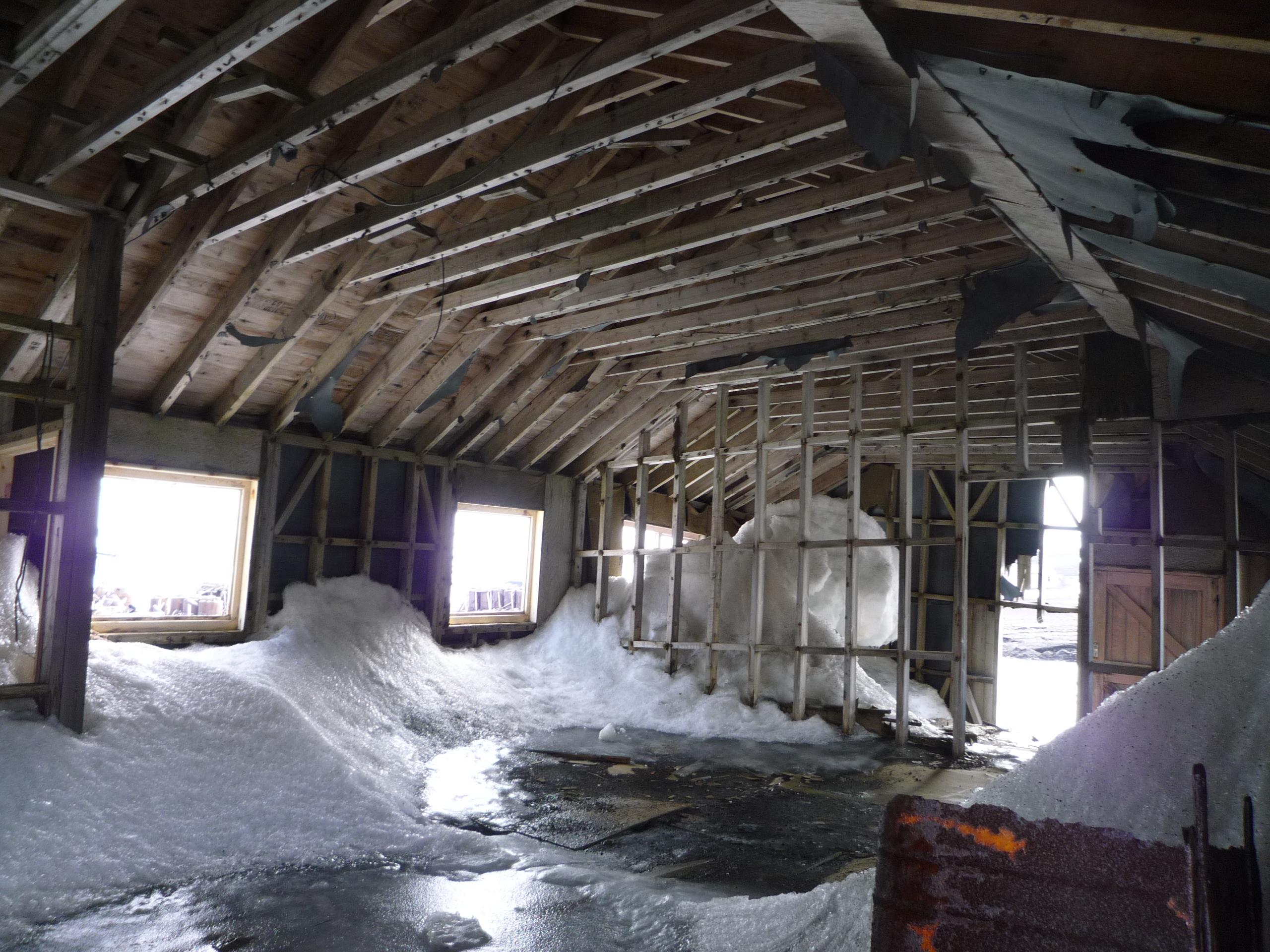 Das historische Gebäude einer Walfangstation in der Antarktis von innen photographiert. Die Tür scheint kaputt. Innen liegt viel Schnee.