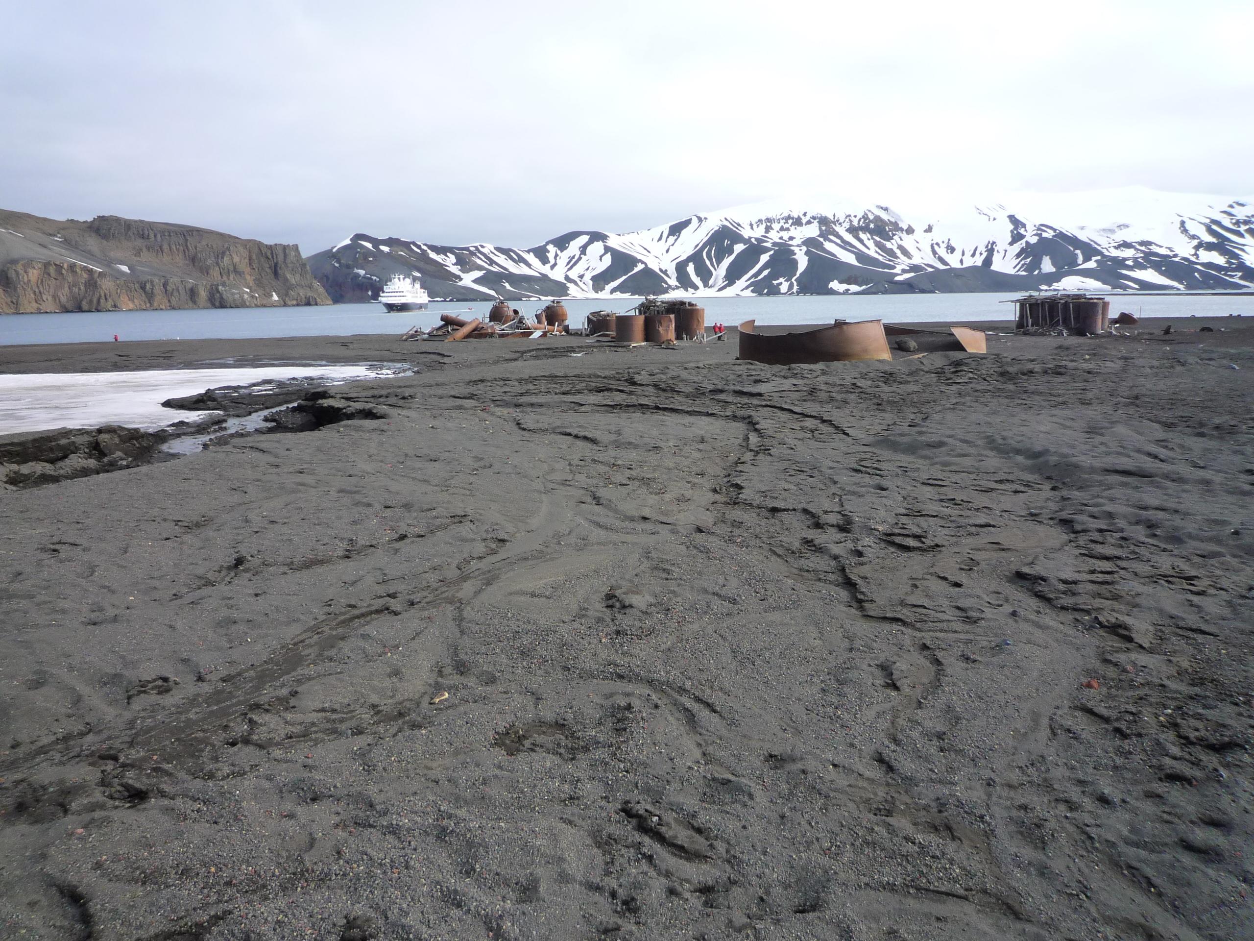 Am erdigen Strand stehen alte, verfallene und verrostete Öltanks. Im Hintergrund sind Berge.