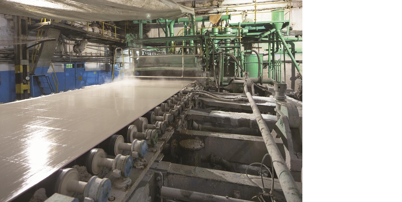 Das Bild zeigt eine Maschine, auf der ein nasser und dampfender Papierstreifen über ein Laufband gezogen wird.