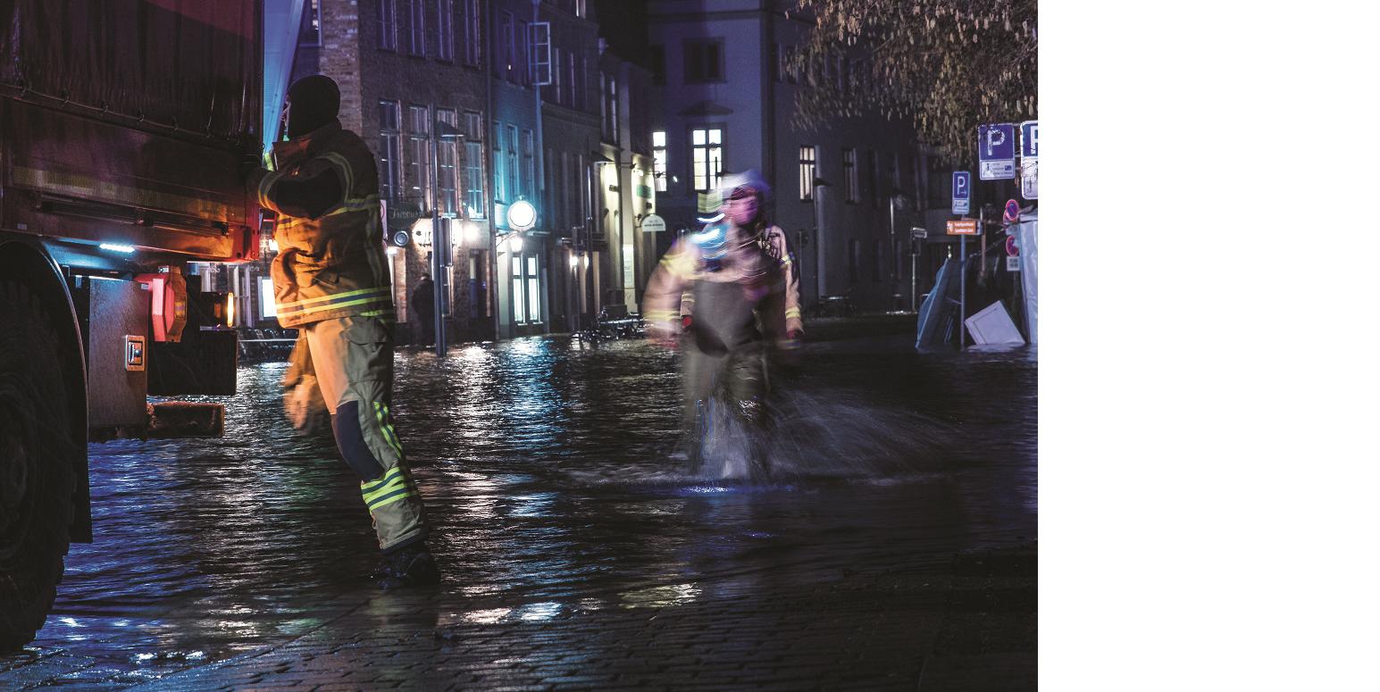Das Bild zeigt einen mit Wasser überfluteten Straßenzug bei Nacht. Zwei Einsatzkräfte waten durch das Wasser, einer davon befindet sich direkt an einem Einsatzfahrzeug.