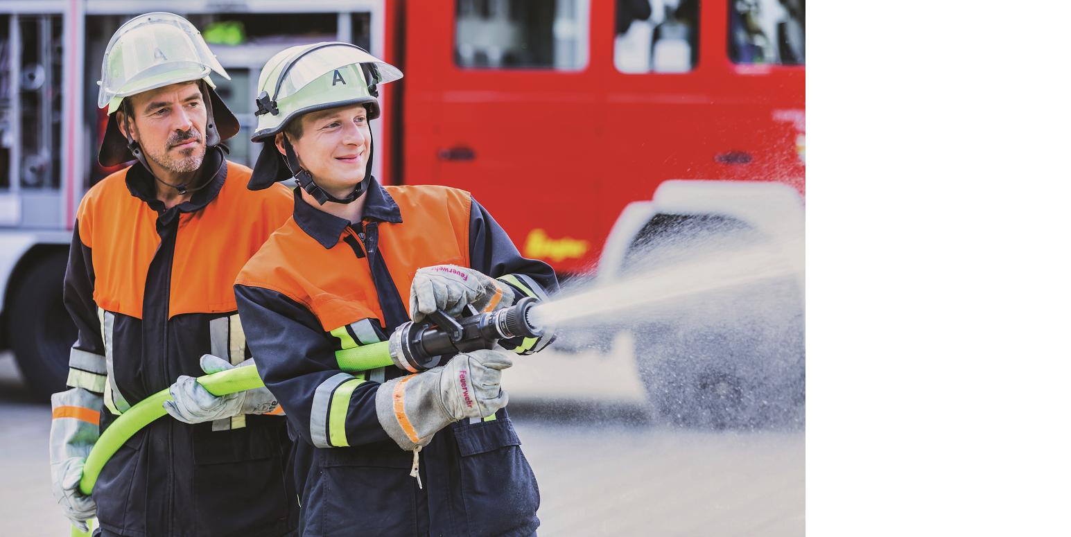 Das Bild zeigt einen jungen, freudestrahlenden Feuerwehrmann, der einen Spritzschlauch betätigt. Hinter ihm steht ein älterer Feuerwehrmann, der ihn offensichtlich anleitet.