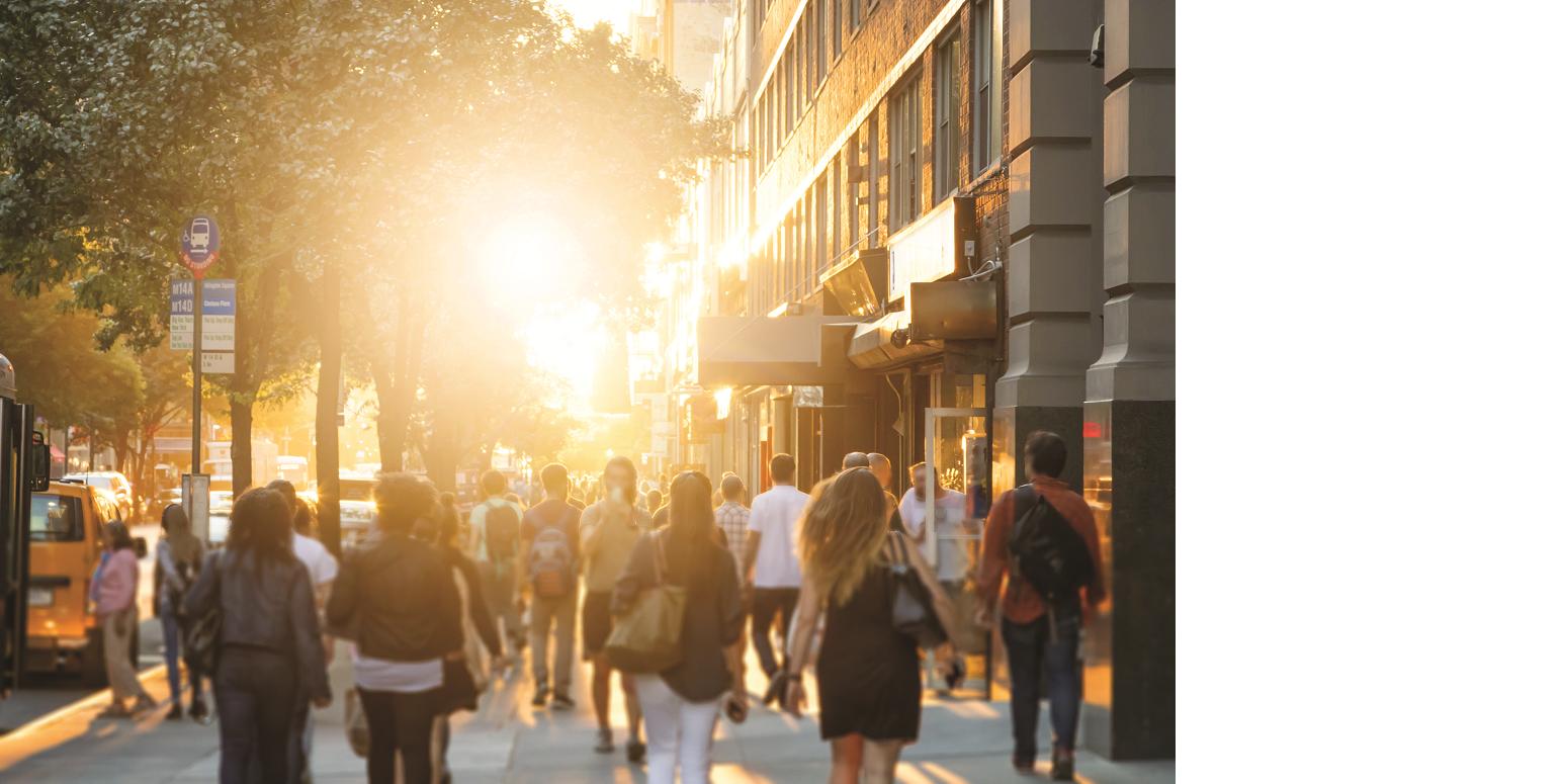 Das Bild zeigt einen dicht bevölkerten Bürgersteig an einer dicht bebauten Straße im Sommer. Die Sonne scheint kräftig und hell im Gegenlicht.
