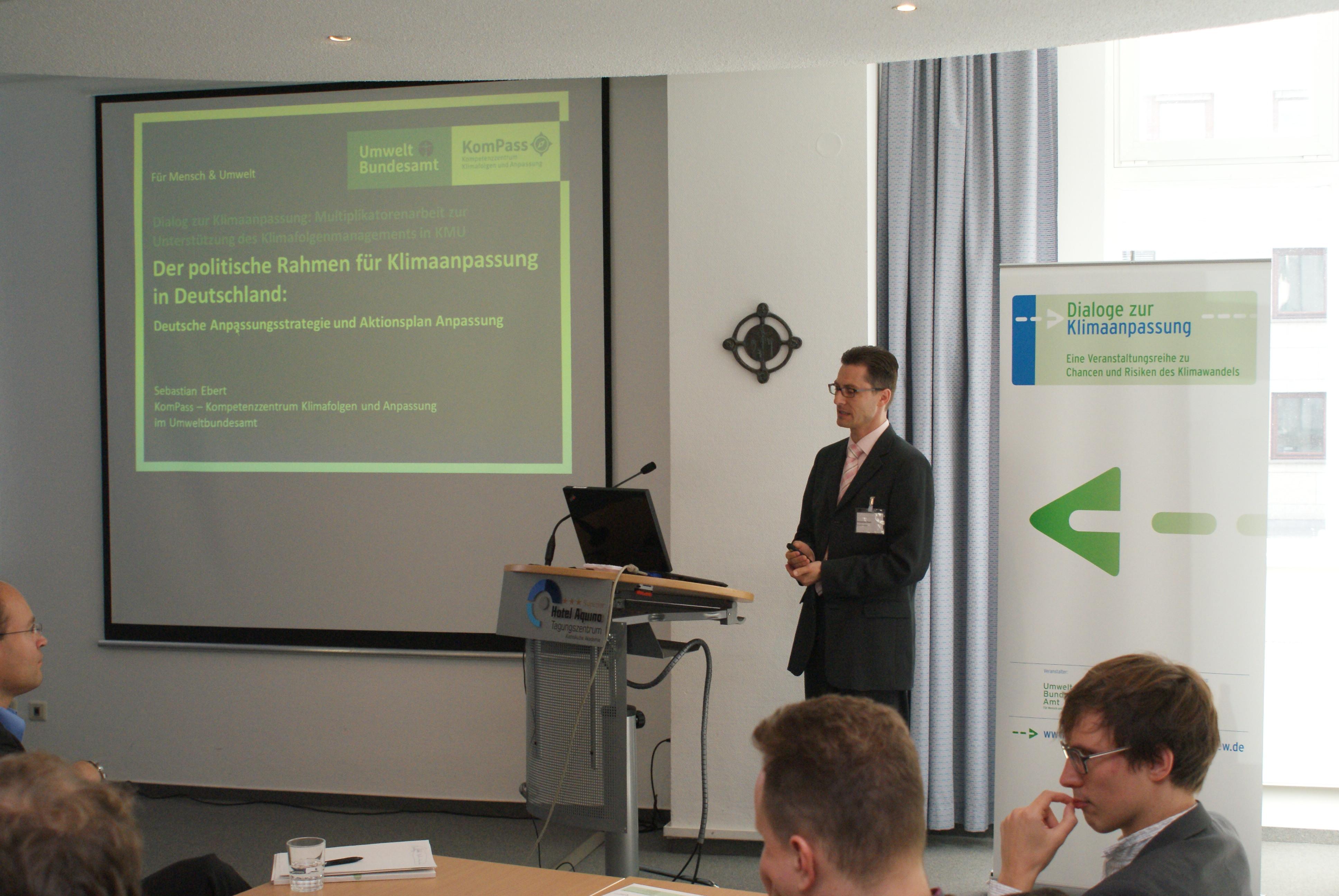 Vortragender steht am Rednerpult. Im Hintergrund sieht man die Präsentation auf Projektionswand und Veranstaltungsaufsteller.