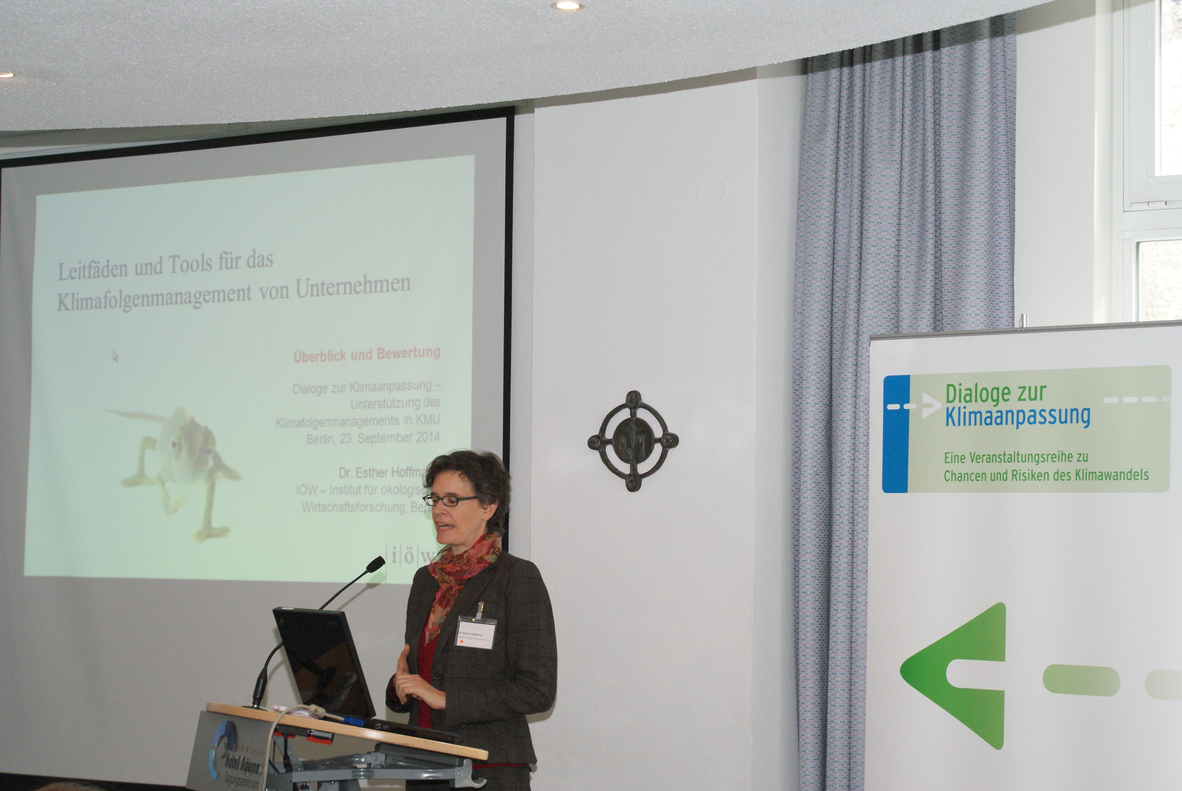 Vortragende steht am Rednerpult und trägt vor. Im Hintergrund sieht man den Vortrag auf der Projektionswand und den Veranstaltungsaufsteller.