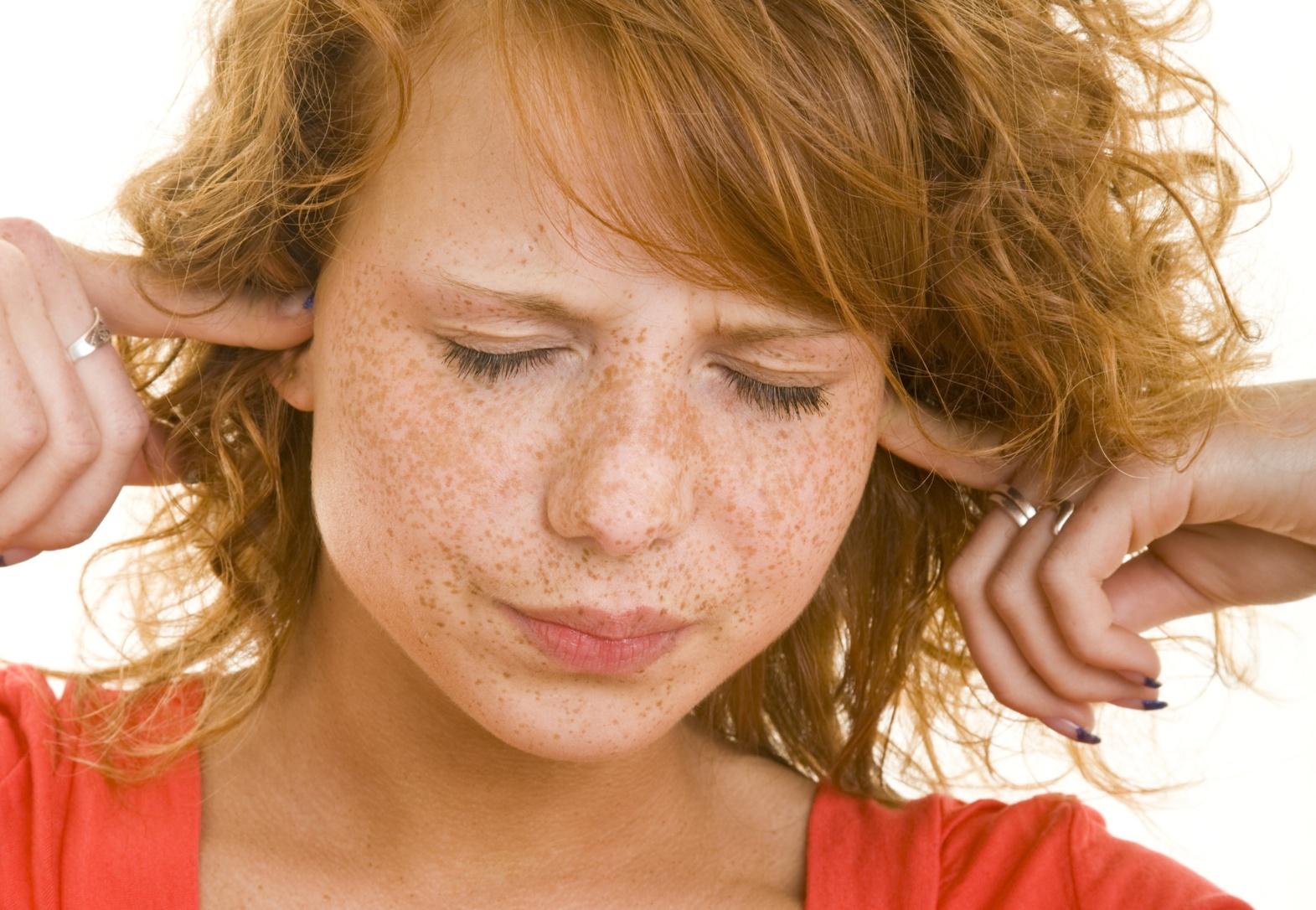 Rothaariges Mädchen hält sich die Ohren zu