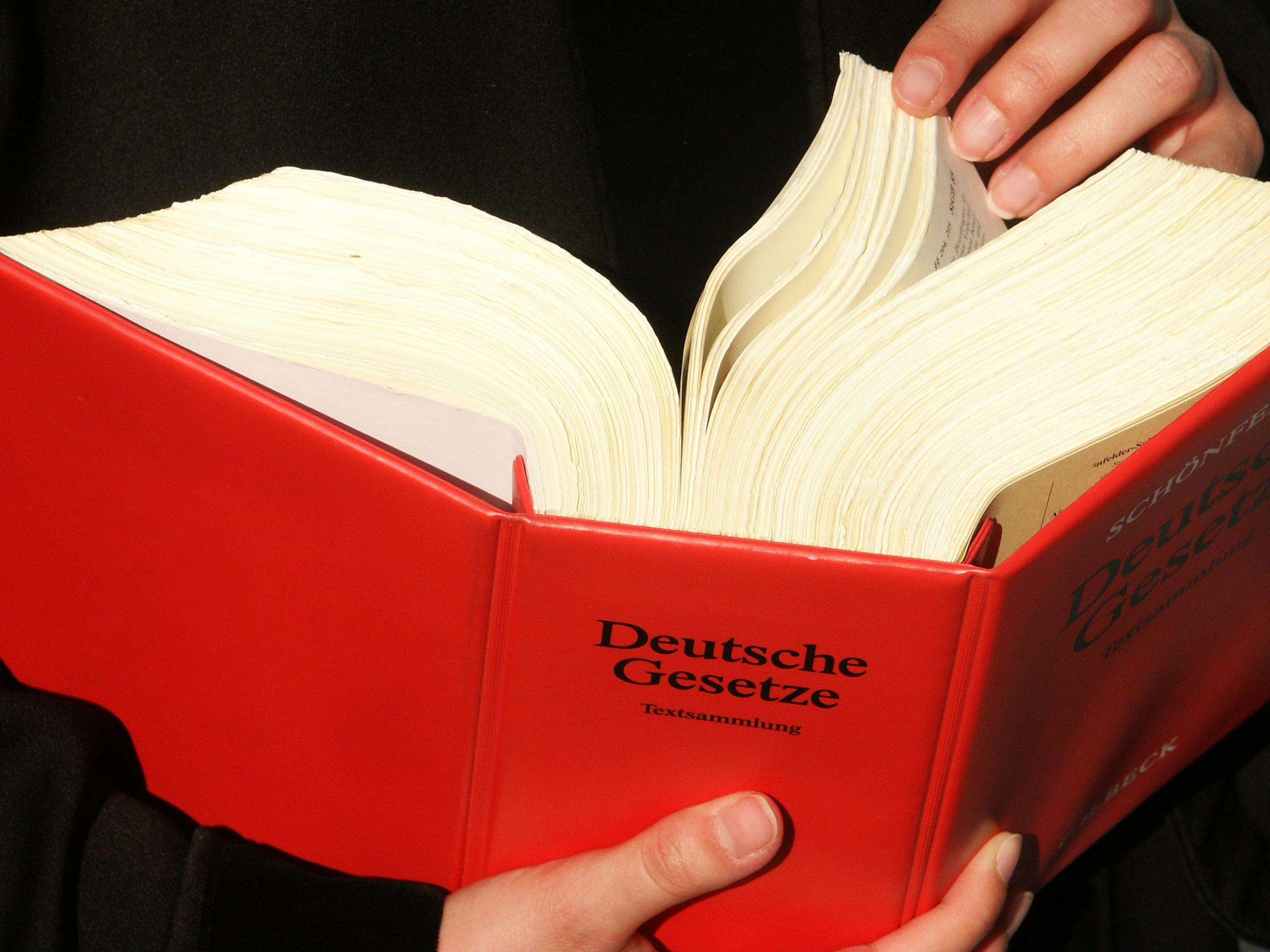 Ein dickes rotes Gesetzbuch, dass umgeblättert wird.