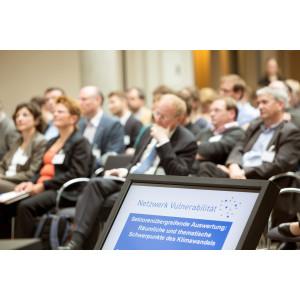 Teilnehmende sitzen und hören einer Präsentation zu