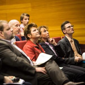 Die Workshopteilnehmer sitzen in Stuhlreihen und hören gebannt den Ausführungen der Vortragenden zu.