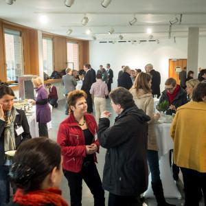 Veranstaltungsteilnehmer die in der Mittagspause in Gruppen zusammenstehen und sich unterhalten und essen und trinken.