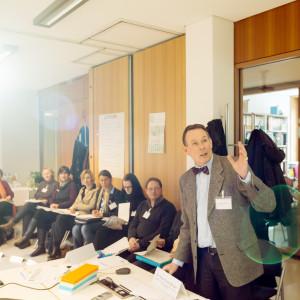 Teilnehmer des Workshops Gesundheit sitzen in einem Stuhlkreis zusammen und hören dem Vortragenden zu