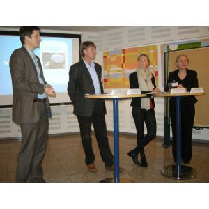 Vier Teilnehmer der Veranstaltung stehen um Bistrotische herum, bereit für eine Podiumsdiskussion