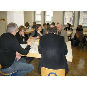 Die Workshopteilnehmer sitzen in kleinen Runden um Tische zusammen und diskutieren.