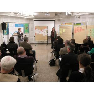 Die Workshopergebnisse in Form von handgeschriebenen Karten die an Pinwänden befestigt sind, werden durch einzelne Workshopteilnehmer vor der gesamten Workshopgruppe vorgestellt.