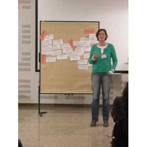 Eine Workshopteilnehmerin stellt Workshopergebnisse, in Form von handgeschriebenen Karten die an Pinwänden befestigt sind, der gesamten Workshopgruppe vor.