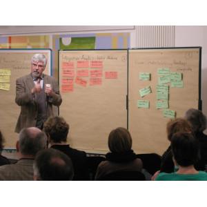Ein Workshopteilnehmer stellt Workshopergebnisse, in Form von handgeschriebenen Karten die an Pinwänden befestigt sind, der gesamten Workshopgruppe vor.