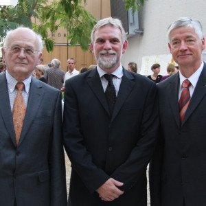 drei Männer im Anzug stehen in einer Reihe aufgestellt im UBA-Gebäude Dessau und schauen in die Kamera