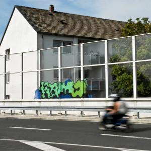 ein Wohnhaus liegt direkt an einer Stadtautobahn hinter einer Lärmschutzwand, gerade fährt ein Motorrad vorbei