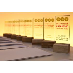 Auf einem Tisch stehen in einer Reihe die Sieger-Trophäen aus Glas mit dem Logo des Bundespreis Ecodesign und dem Namen des jeweiligen Preisträgers