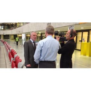 Jochen Flasbarth wird in einem Stadion von einem Reporter interviewt, ein Kameramann filmt