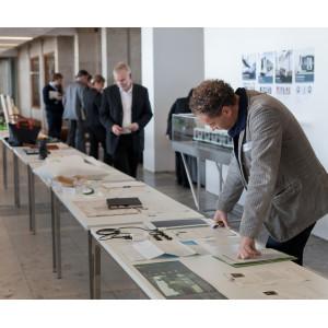 Auif einer langen Tischreihe liegen Produkte und Ausdrucke, die von mehreren Personen angeschaut werden