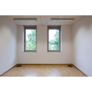 leerer Büroraum mit weißen Wänden und Holzfußboden, durch die zwei Fenster sind grüne Baumkronen zu sehen