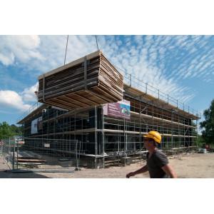 eingerüstetes Haus, davor ein Bauarbeiter mit gelbem Helm, ein Kran liefert Elemente für die Holz-Fassadenverkleidung an