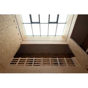 Innenansicht des Gebäudes im Rohbauzustand, die Innenwände aus rohen Holzwerkstoffplatten, durch ein Glasdacht fällt Tageslicht durch das Treppenhaus bis ins Erdgeschoss