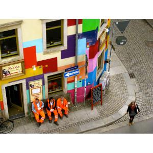 Drei Männer in den orangenen Anzügen der Müllabfuhr sitzen auf einer Bank vor einem bunt gestrichenen Eckhaus und trinken Kaffee