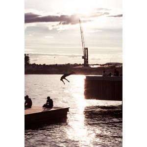 Im Hafen von Oslo: Bei untergehender Sonne springt ein Mann von einem Steg ins Wasser, davor sieht man zwei Personen, die in der Abendsonne sitzen.