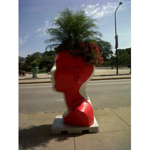 Auf dem Bürgersteig steht ein übergroßer roter Kopf, er dient als Blumentopf.