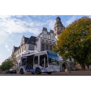 Ein mit Wasserstoff betriebener Kleinbus steht auf der Straße vor einem alten Gebäude und einem Baum