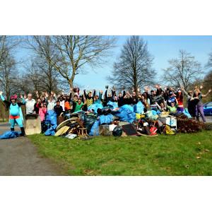 Gruppenfoto von etwa 30 Personen nach einer Müllsammelaktion im Wald und freien Feld. Einige Personen sind verkleidet, im Vordergrund liegt der gesammelte Müll.