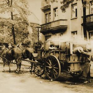 Ein Arbeiter entleert einen Eimer au offene Ladefläche eines Pferdewagens.