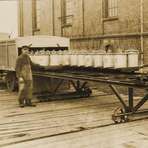 Zwei Männer tauschen Eimer auf einem auf Schienen laufenden Wagen aus.