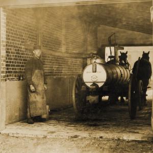 Ein Mann steht mit einem Jauchewagen in einer Einfahrt, der Wagen trägt einen Metalltank und wird von zwei Pferden gezogen.