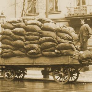 Ein Arbeiter steht auf der Ladefläche eines Pferdewagens, auf der viele Säcke gestapelt sind. Davor steht eine Leiter, über die er auf den Wagen gekommen ist.