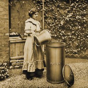 Eine Frau entsorgt müll aus einem kleinen Hauseimer in einen hohen Standeimer.