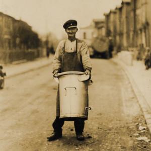 Ein Mann trägt eine hohe Mülltonne auf der Straße