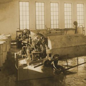 Bürstenwaschmaschine in einem Fabrikgebäude, ein Arbeiter zieht eine Tonne aus der Maschine