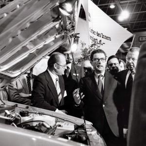 mehrere Männer stehen in einer Messehalle um ein Auto mit geöffneter Motorhaube herum.