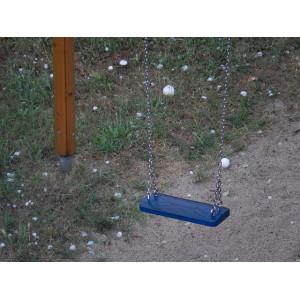 Eine Schaukel blaue Schaukel. Auf dem Boden liegen viele große Hagelkörner.
