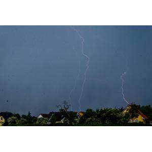 Ein dunkler Himmel mit Blitzen über Häusern.