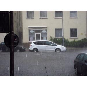 Eine überschwemmte Straße mit geparkten Autos
